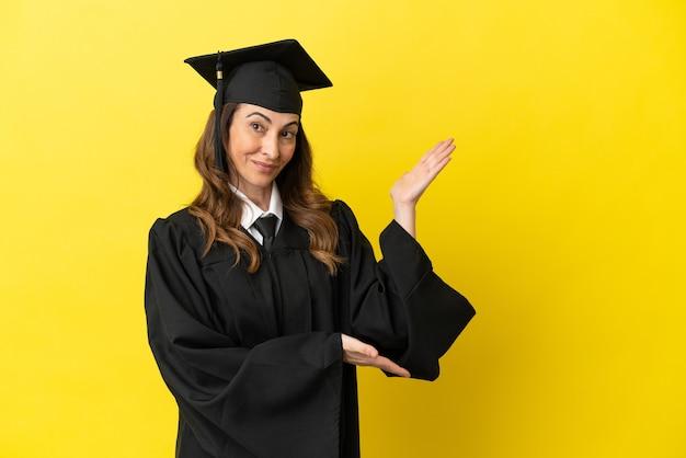 Universitair afgestudeerde van middelbare leeftijd geïsoleerd op een gele achtergrond die de handen naar de zijkant uitstrekt om uit te nodigen om te komen
