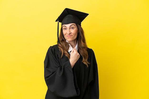 Universitair afgestudeerde van middelbare leeftijd geïsoleerd op een gele achtergrond die een overwinning viert