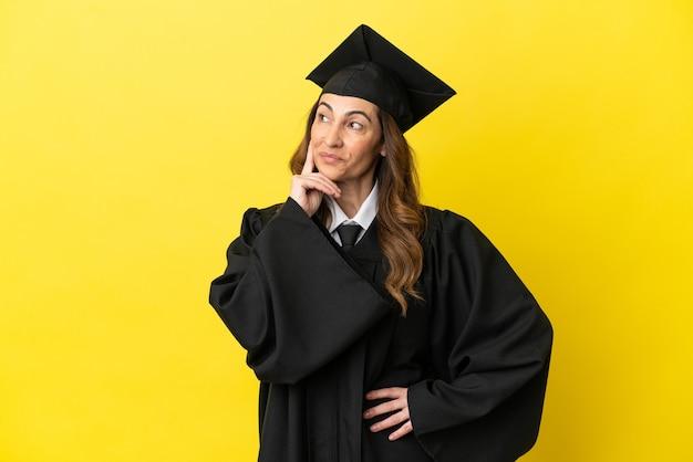 Universitair afgestudeerde van middelbare leeftijd geïsoleerd op gele achtergrond die een idee denkt terwijl hij omhoog kijkt