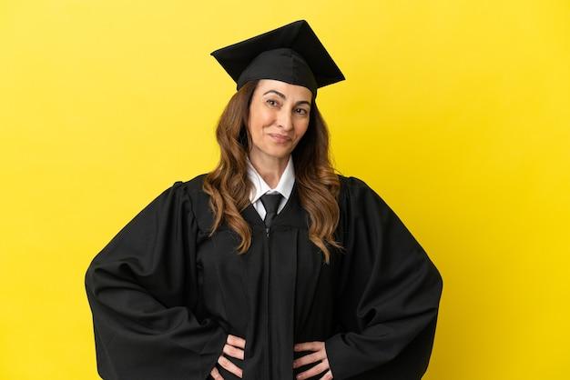 Universitair afgestudeerde van middelbare leeftijd geïsoleerd op gele achtergrond lachen