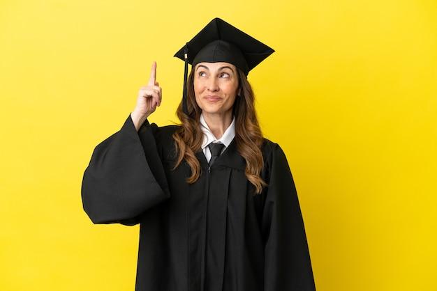 Universitair afgestudeerde van middelbare leeftijd geïsoleerd op gele achtergrond met de bedoeling de oplossing te realiseren terwijl hij een vinger opsteekt