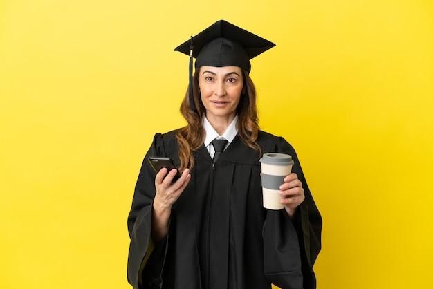 Universitair afgestudeerde van middelbare leeftijd geïsoleerd op gele achtergrond met koffie om mee te nemen en een mobiel