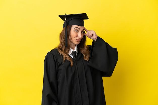 Universitair afgestudeerde van middelbare leeftijd geïsoleerd op gele achtergrond met twijfels en met verwarde gezichtsuitdrukking