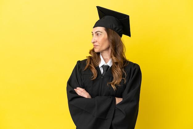 Universitair afgestudeerde van middelbare leeftijd geïsoleerd op gele achtergrond op zoek naar kant