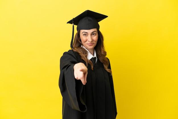 Universitair afgestudeerde van middelbare leeftijd geïsoleerd op gele achtergrond wijst vinger naar je met een zelfverzekerde uitdrukking
