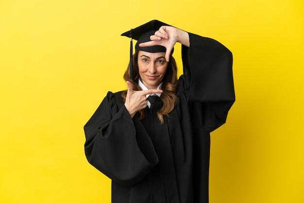 Universitair gediplomeerde van middelbare leeftijd geïsoleerd op gele achtergrond gericht gezicht. frame symbool