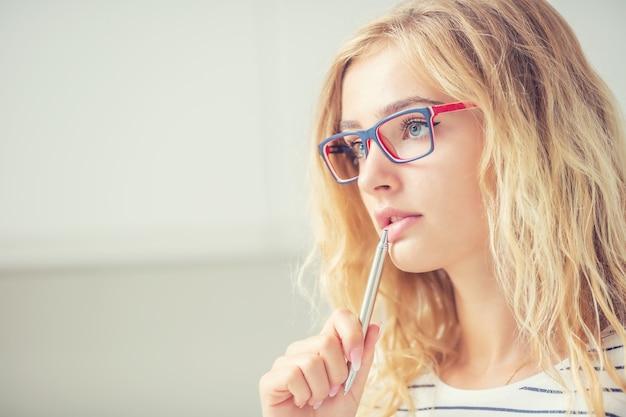 Universitair studentenmeisje peinzend met pen op haar lippen. portret van denkende vrouw met een bril.