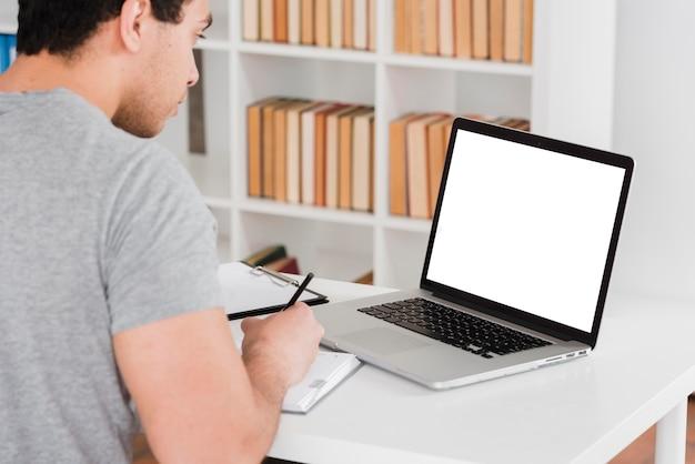 Universitaire student die op laptop werkt