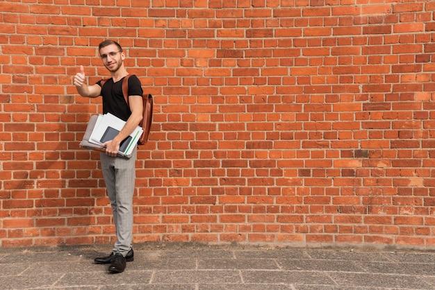 Universitaire student die zich voor een ruimteachtergrond van het bakstenen muurexemplaar bevindt