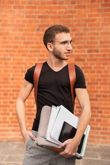 Universitaire student die zijn nota's houdt en weg kijkt