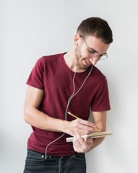 Universitaire student draagt een koptelefoon en schrijven