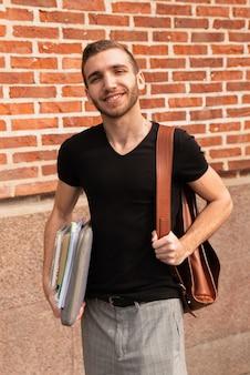 Universitaire student met genoteerd en rugzak die bij camera glimlacht