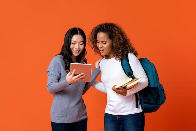 Universitaire studenten als vrienden die tabletcomputer bekijken