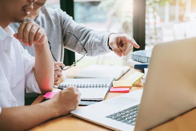 Universitaire studenten die laptop vergadering voor onderzoekthuiswerk gebruiken op universiteit