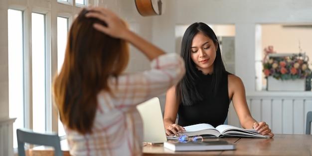 Universitaire studenten lezen samen in de woonkamer een boek.