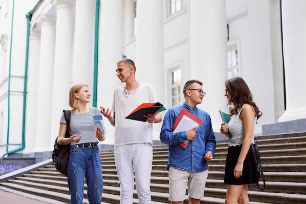 Universitaire studenten met boeken voor universiteitsgebouw