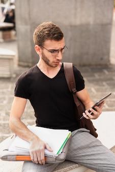 Universitaire studentenzitting op een bank en het fronsen bij tablet