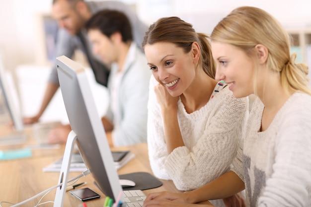 Universiteitsmeisjes die voor desktop werken