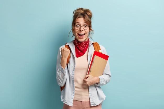 Universiteitsstudent met blije uitdrukking, steekt gebalde vuist op, viert geslaagd examen, krijgt uitstekend cijfer