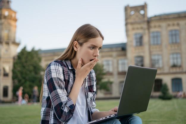 Universiteitsstudent met geschokt bang gezicht dat slecht nieuws leest, examens mislukt. vrouw freelancer met laptopcomputer, ze miste deadline