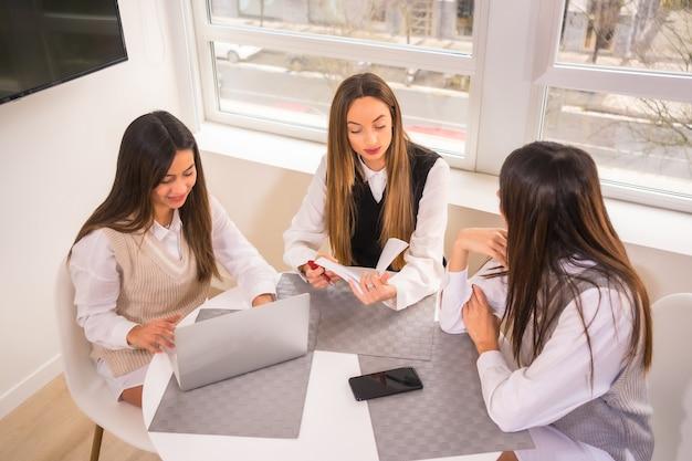 Universiteitsvrienden in een informele bijeenkomst met computers en mobiele telefoons, die het examen terugkijken voordat ze naar de universiteit gaan.