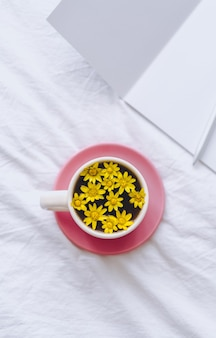 Ð¡up met gele bloemen erin, op een wit bed met blocnote en pen.