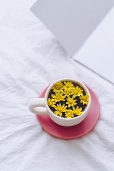 Ð¡up met gele bloemen erin, 's ochtends op een wit bed met blocnote
