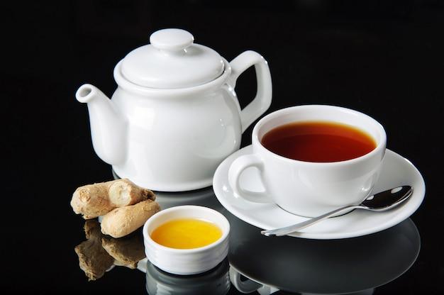 ? up van zwarte thee met honing en gember op een zwarte