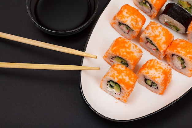 Uramaki californië. sushibroodjes met nori, rijst, stukjes avocado, komkommer, versierd met vliegende viskuit op keramische plaat. kom met sojasaus en houten stokken. japanse keuken. bovenaanzicht.