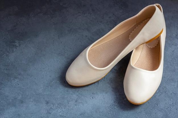 Urban damesschoenen: beige flats, instapper. casual zomer schoenen op donkere achtergrond. vrouwen- of tienermode.