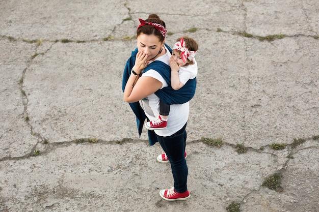 Urban family look van moeder en baby meisje in draagdoek draagdoek