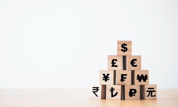Us dollar print scherm op houten kubus bovenop renminbi yuan yen euro en pond sterling teken. amerikaanse dollar is de belangrijkste en populaire valuta van de wereld. investerings- en besparingsconcept.