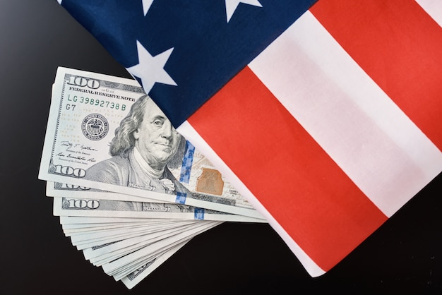 Usa nationale vlag en dollarbiljetten op donker. zakelijke en financiële concept