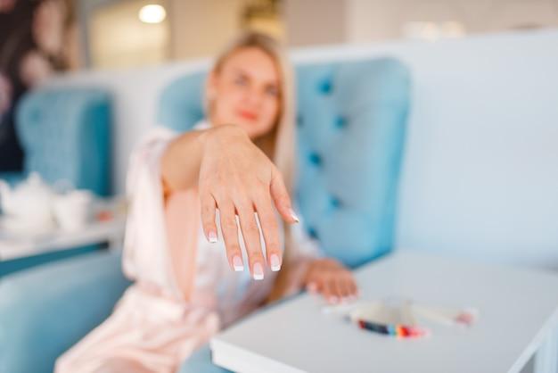 Сustomer toont perfect gemaakte nagels in schoonheidssalon
