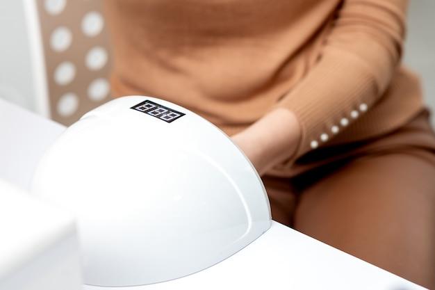 Uv-lamp gel polish manicure machine tijdens proces voor het drogen van nagels in de schoonheidssalon