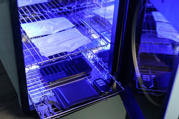 Uv-licht sterilisatie van mobiele telefoon en gezichtsmasker tot desinfectie. covid-19-preventieconcept. ultraviolette sterilisatie en desinfectie.