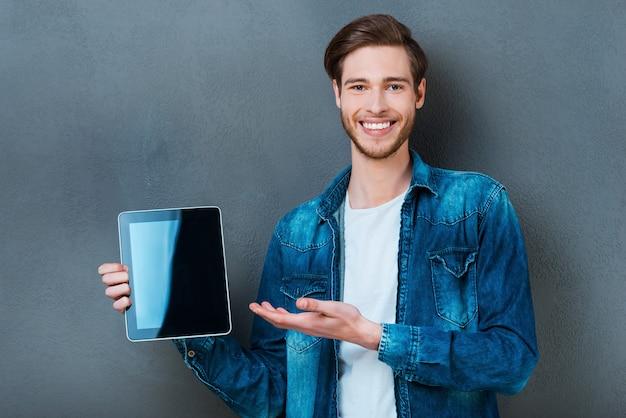 Uw advertentie op zijn digitale tablet. glimlachende jonge man met digitale tablet