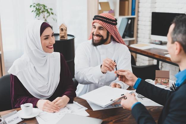 Uw handtekeningagent geeft pen aan arabische klant.