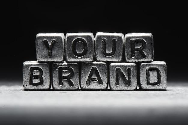 Uw merkconcept. 3d-inscriptie op metalen blokjes op een grijze zwarte achtergrond geïsoleerd