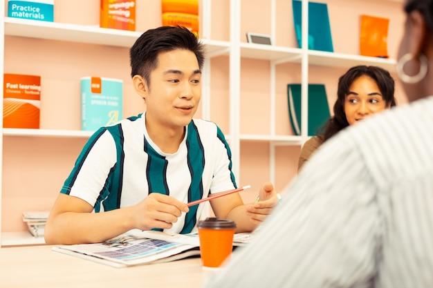 Uw termijn. vrolijke aziatische student die positiviteit uitdrukt terwijl hij tijd doorbrengt in een spreekclub