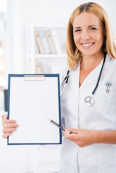 Uw testresultaten hier. gelukkig vrouwelijke arts in wit uniform camera kijken en glimlachen