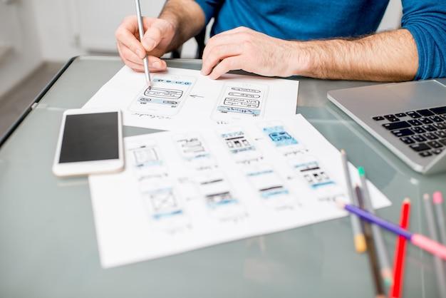 Ux-ontwerper werkt aan de mobiele applicatie-ervaring met het schetsen van tekeningen op kantoor. afbeelding gefocust zonder de tekeningen bijgesneden zonder gezicht