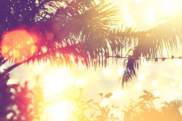 Vaag licht bokeh met de achtergrond van de kokosnotenpalm op zonsondergang, gele koordlichten met bokehdecor in openluchtrestaurant