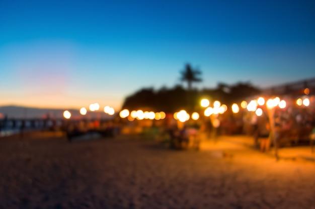 Vaag zeevruchtenrestaurant bij het strand met mooie zonsonderganghemel als achtergrond