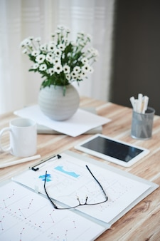 Vaas met bloemen, map met rapporten, bril en tabletcomputer op tafel van thuiswerkende persoon