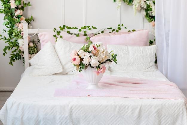 Vaas met bloemen op het bed. bloemen woondecoratie.
