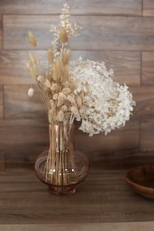 Vaas met boeket gedroogde hortensia aartjes en planten houten tafel herfst woondecoratie
