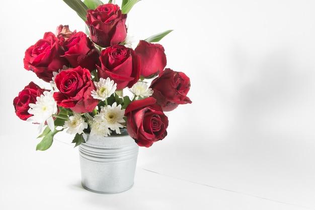 Vaas met boeket rode rozen in aluminium emmer op witte achtergrond.