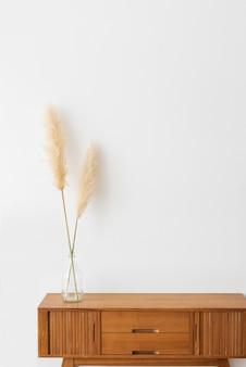 Vaas met droog pampagras op een houten kast in een witte kamer