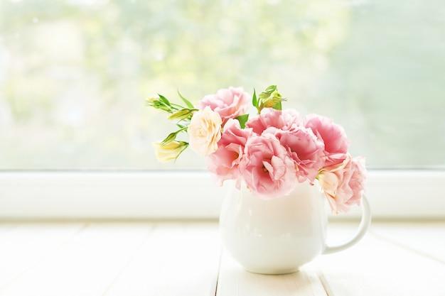 Vaas met eustoma bloemen op een tafel tegen een raam